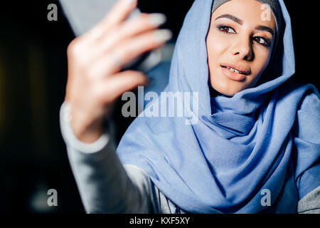 Arabian muslim woman taking selfie with phone in cafe - Stock Photo