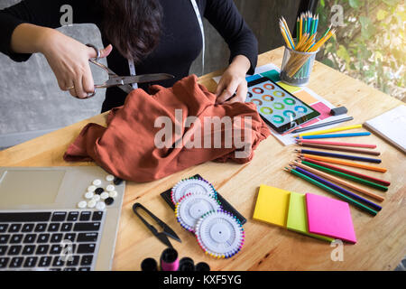 Hands notch tailor tailor's scissors cloth cutting a piece of fabric (fashion designer concept) - Stock Photo