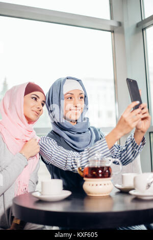 excited young muslim girl friends taking selfie together - Stock Photo
