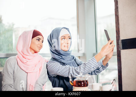 two happy young muslim woman take self portrait with handphone at cafe - Stock Photo