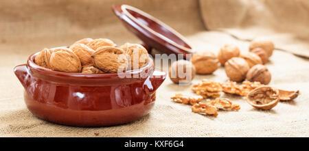 Walnuts in a ceramic pot on a burlap - Stock Photo