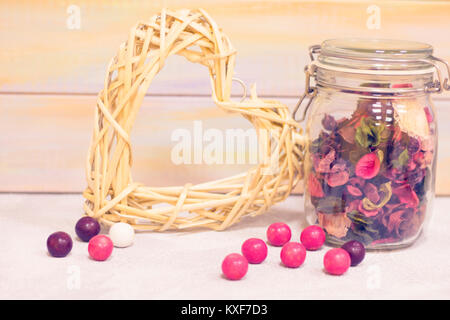 Romantic composition- A glass clear jar with dry flowers and rose petals, a yellow woven heart wreath and round - Stock Photo