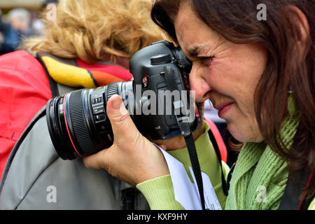 Portrait of woman photographer holding large DSLR camera when taking a photograph - Stock Photo