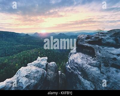 Morning view over sandstone cliff into misty valley. Sandstone peaks increased from foggy cloud, warm colors. - Stock Photo