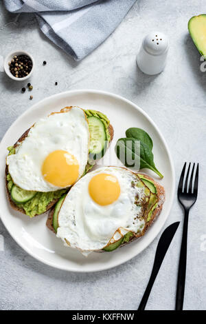 Fried egg, avocado and cucumber on whole grain toasted bread . Healthy eating, healthy breakfast food concept - Stock Photo