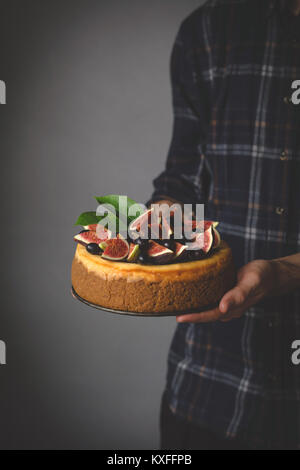 Holding cheesecake in hands. Homemade cheesecake with fruits in male hands. Selective focus - Stock Photo