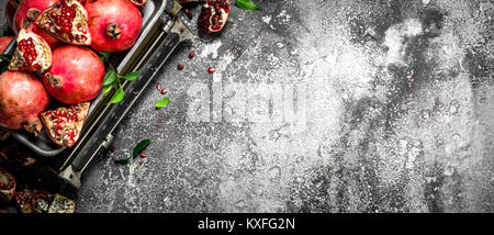 Ripe pomegranates on the scales. On a rustic background. - Stock Photo