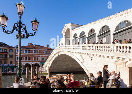 Tourists sitting at tables below the Rialto Bridge, Grand Canal, San Marco, Venice, Italy eating and drinking in - Stock Photo