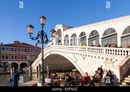 Tourists at an open air restaurant below  Rialto Bridge, Grand Canal, San Marco, Venice, Italy enjoying sundowners - Stock Photo