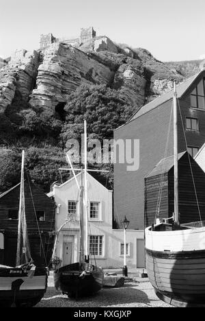 Net huts and boats on the beach at Hastings, East Sussex, with East Hill in background - Stock Photo