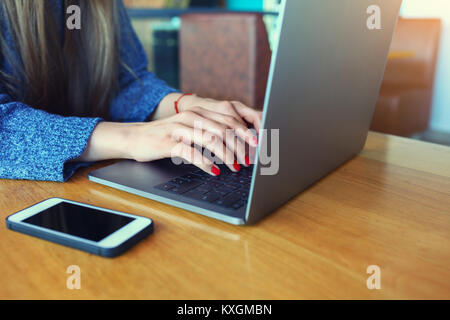 Close up of women's hands. Woman working on laptop in a cafe. Young woman sitting at a table with a coffee usinglaptop. - Stock Photo
