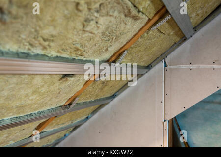 Attic under construction wooden roof frame and plastic for Rocks all insulation