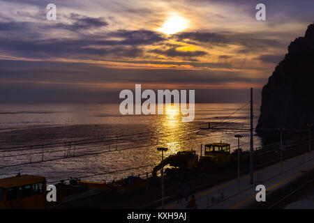 The sunset and the sea on the coast of Monterosso Al Mare in Cinque Terre Italy taken from the train station - Stock Photo