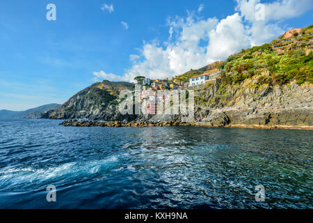 The rocky coastline of Riomaggiore Italy, part of the colorful villages of Cinque Terre Italy at the Ligurian Sea - Stock Photo