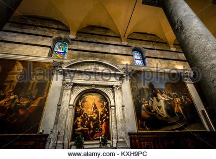 Renaissance religious paintings at the side altar of the Pisa Cathedral in Pisa Italy showing the gothic interior - Stock Photo