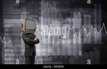 Businessman in suit with old TV instead of head keeping arms crossed while standing against analytical charts drawn - Stock Photo