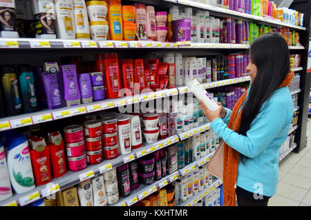 Portugal, Algarve, Monchique, Circa 10 December. 2013. Young woman selecting shampoo from a supermarket. Image taken - Stock Photo