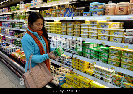 Portugal, Algarve, Monchique, Circa 10 December 2013. Young woman choosing Butter and margarine in a supermarket. - Stock Photo