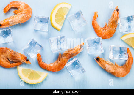 Fresh shrimp with lemon on ice on blue table, top view. Culinary seafood eating. - Stock Photo