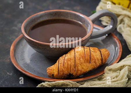 Cup of fragrant coffee and a croissant. Morning breakfast - Stock Photo