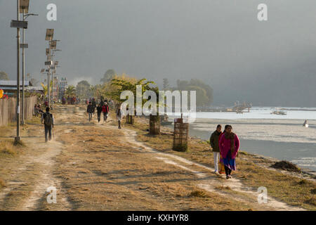 People walking along the edge of Phewa Lake in Pokhara, Nepal - Stock Photo