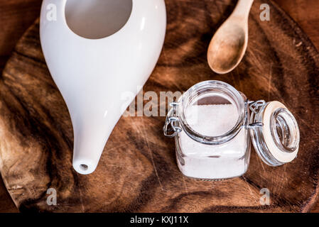 neti pot, ayurvedic tools for cleaning nose with water and salt, view from top, wooden table and board on background - Stock Photo