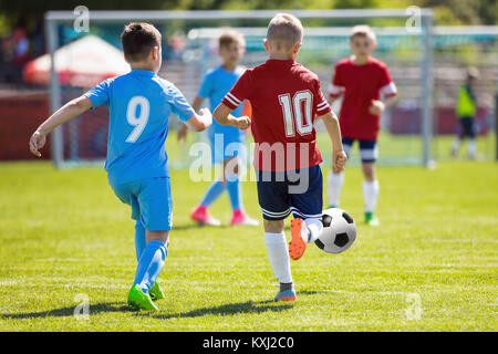 Running Soccer Football Players. Footballers Kicking Football Match. Soccer School Tournament. Young Soccer Players - Stock Photo