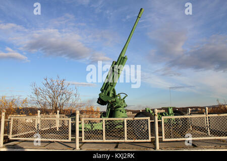 Green anti-aircraft gun near monument of soviet soldiers in Murmansk, Russia - Stock Photo