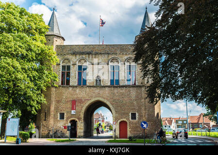 Bruges, Belgium, - August 31, 2017: Gentpoort (Gate of Ghent) with people circulating on bike in the medieval city - Stock Photo