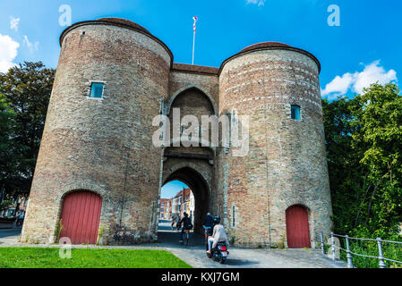 Bruges, Belgium, - August 31, 2017: Gentpoort (Gate of Ghent) with people circulating on bike and motorbike in the - Stock Photo