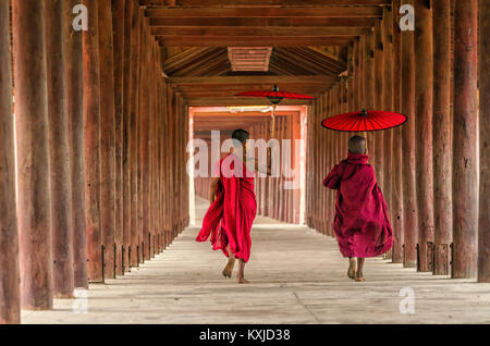 Back side of two young monk holding the traditional umbrella on the Mya Thein Tan Pagoda at bagan, mandalay, myanmar - Stock Photo