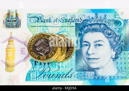 New british five pound note with one pound coins, isolated on white background. - Stock Photo
