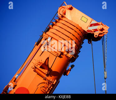 Zoom shot of an orange-coloured truck-mounted crane with telescopic boom pushed together, blue sky - Stock Photo