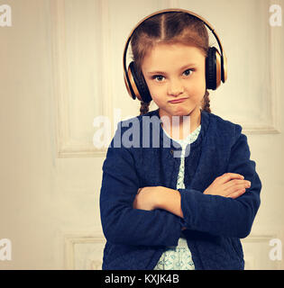 Angry grimacing kid girl in blue jacket listening the music in wireless headphone with folded arms on studio background. - Stock Photo