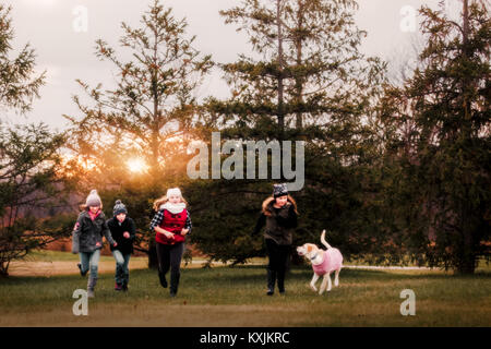 Boy and three female cousins running with dog in garden - Stock Photo