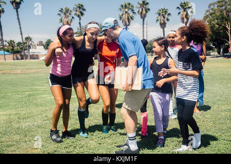Schoolgirl soccer team and teacher supporting injured player on school sports field - Stock Photo
