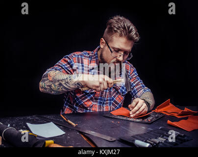 Man working with leather demostrating leather cutting process at his leather shop - Stock Photo