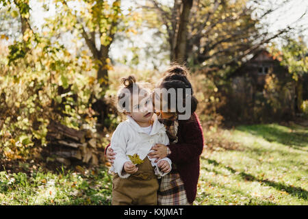 Girl hugging younger sister, in rural setting - Stock Photo