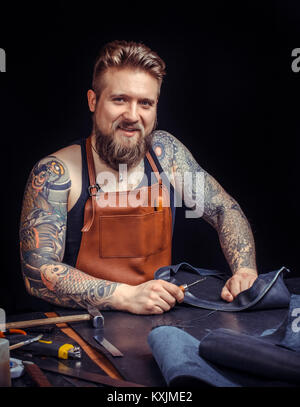 Craftsman at work on his new leather product - Stock Photo