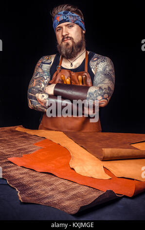 Leather Worker focusing on his work in the leather shop - Stock Photo