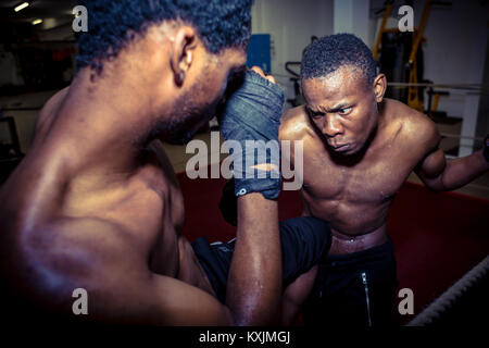 Determined offensive fighter hitting his opponent while practici - Stock Photo
