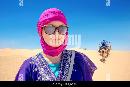 Portrait of beautiful woman in arabic traditional clothing against background of tourists riding on camels. Sahara - Stock Photo