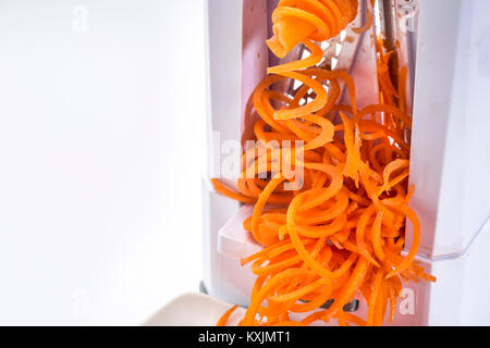 fresh raw carrot being processed with spiralizer (spiral slicer) - Stock Photo