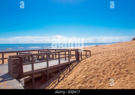 Empty wooden walkway entrance onto sandy beach against sea and blue cloudy sky landscape at Mtunzini in South Africa - Stock Photo