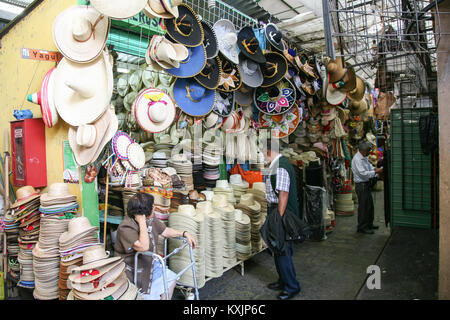 OAXACA, MEXICO - MARCH 7th, 2012: Woman selling large variety of mexican traditional hats and sombreros on a local - Stock Photo