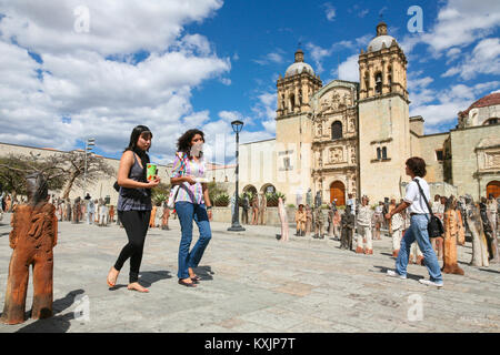 OAXACA, MEXICO - MARCH 7th, 2012: People walk by the Church of Santo Domingo de Guzman in Oaxaca, Mexico - Stock Photo