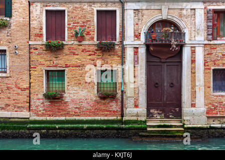 Facade of partially mossy old brick house with wooden vintage door on narrow canal in Venice, Italy. - Stock Photo