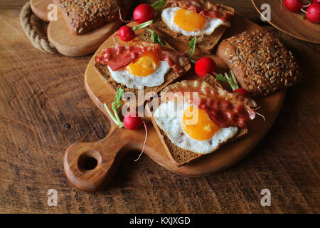Breakfast of crispy bacon, fried eggs and bread. Sandwiches on cutting board. Rustic table - Stock Photo