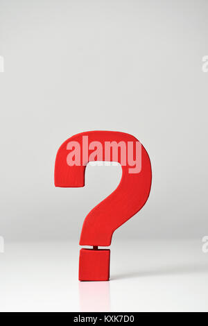 a red three-dimensional question mark on an off-white background, with a blank space on top - Stock Photo