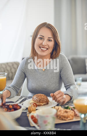Happy attractive woman enjoying a sandwich for breakfast sitting at a table laid with food smiling at the camera - Stock Photo